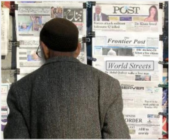 man reading newspapers newsstand
