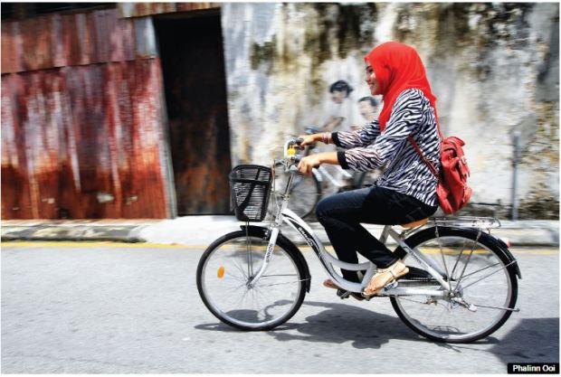 Penang girl on bike - covered head